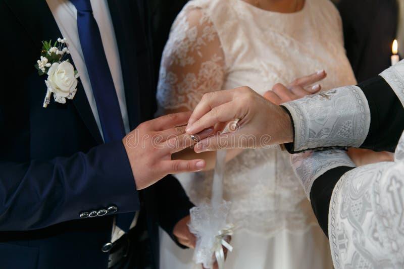 El sacerdote cambia los anillos de bodas en los fingeres de la novia y del novio imagen de archivo libre de regalías