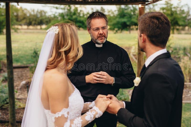 El sacerdote casa un par en ceremonia preciosa fotos de archivo libres de regalías