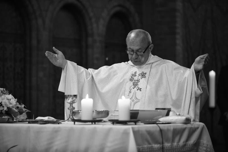 El sacerdote católico dice rezos foto de archivo