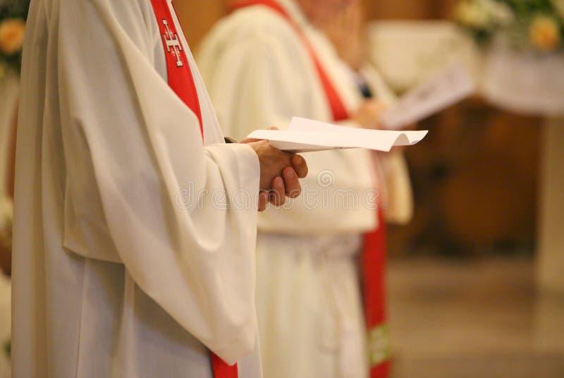 El sacerdote con las manos se unió a en rezo durante la misa santa en iglesia imagen de archivo libre de regalías