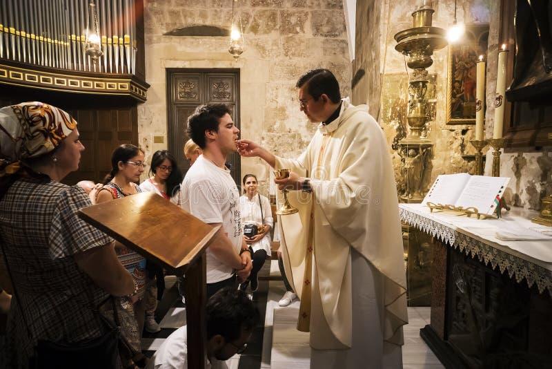 El sacerdote de la iglesia de Santo Sepulcro da la comunión santa al hombre fiel con otros creyentes que esperan su vuelta jerusa foto de archivo