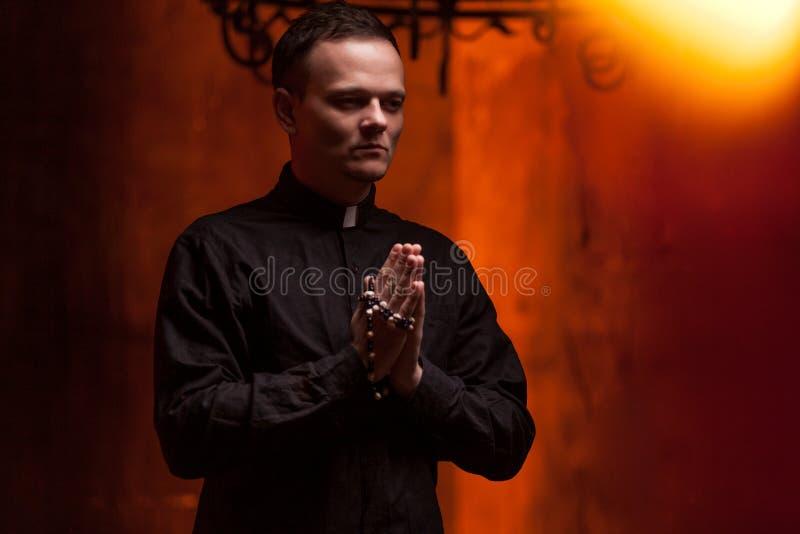 El sacerdote de rogación católico joven Portrait del sacerdote al lado de las velas ruega con sus manos imagen de archivo libre de regalías