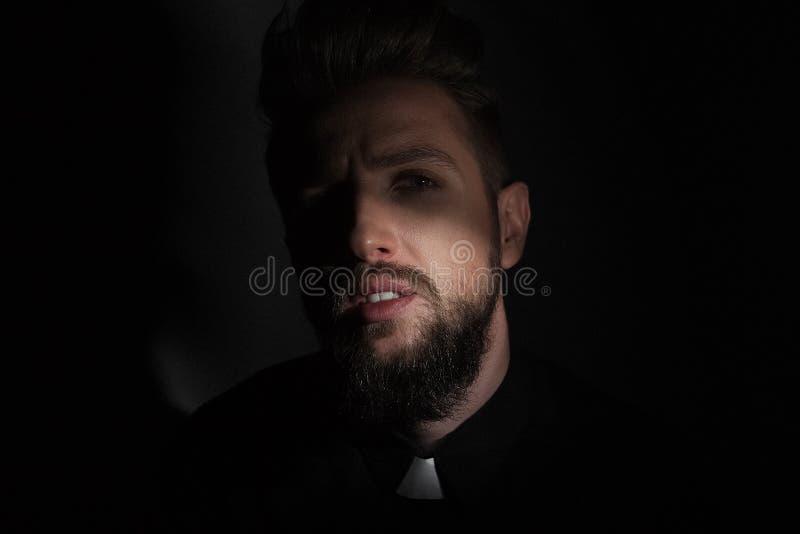 El sacerdote es una cara grande en el crepúsculo que mira la cámara en un fondo gris fotografía de archivo