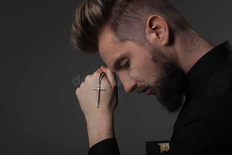 El sacerdote lleva a cabo una mano con una cruz el al frente en un fondo gris fotografía de archivo