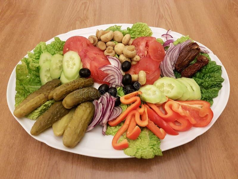 El salade mediterráneo con los tomates, aguacate, mozzarella, menta y ensaladilla de las aceitunas, aisló la placa en un fondo bl fotos de archivo libres de regalías