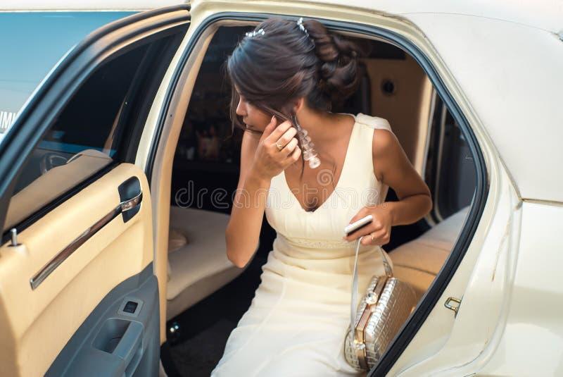 El salir atractivo joven de la mujer del VIP de la limusina con la puerta que está abierta foto de archivo libre de regalías