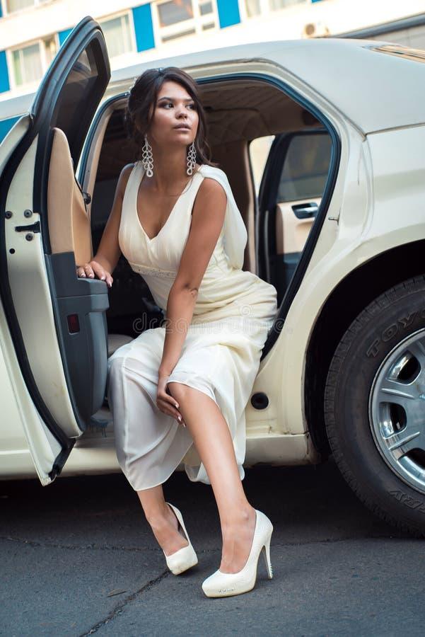 El salir atractivo joven de la mujer del VIP de la limusina con la puerta que está abierta imagen de archivo