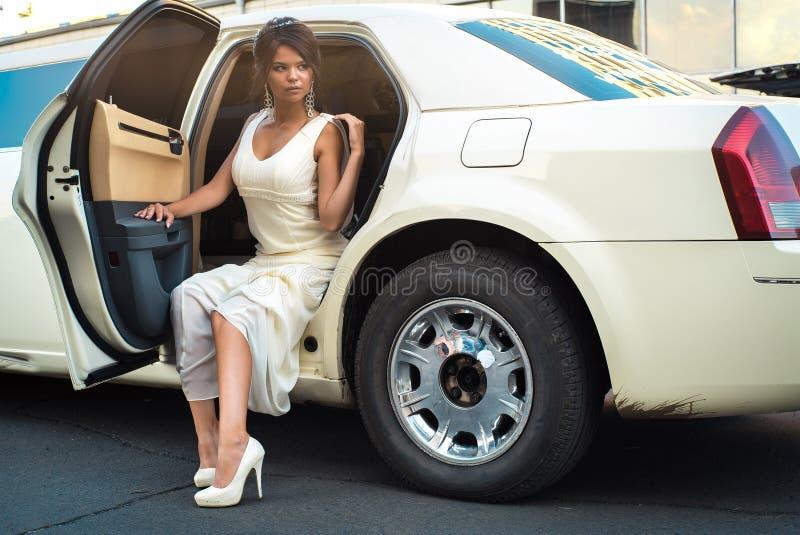 El salir atractivo joven de la mujer del VIP de la limusina con la puerta que está abierta imagen de archivo libre de regalías