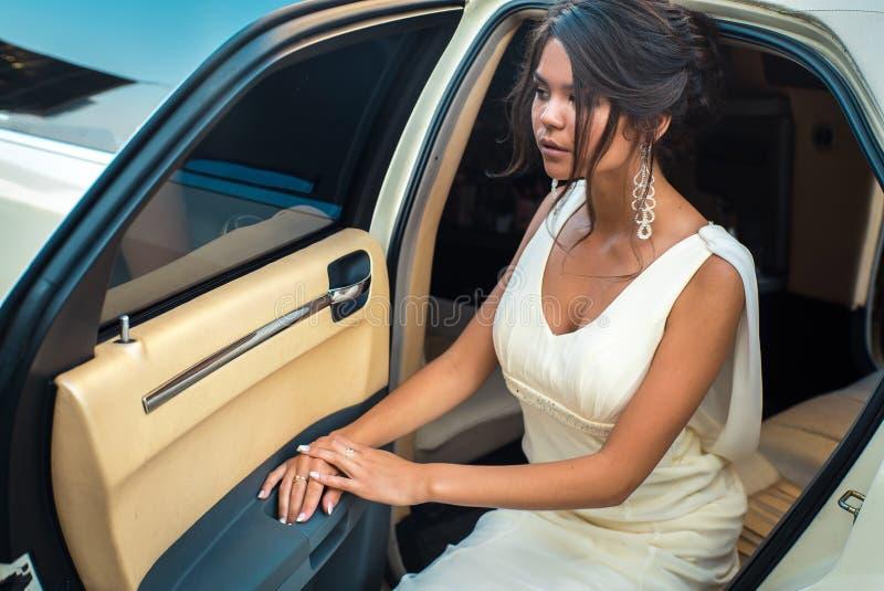 El salir atractivo joven de la mujer del VIP de la limusina con la puerta que está abierta fotos de archivo libres de regalías