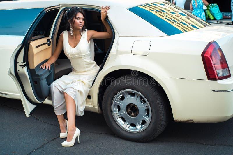 El salir atractivo joven de la mujer del VIP de la limusina con la puerta que está abierta imágenes de archivo libres de regalías