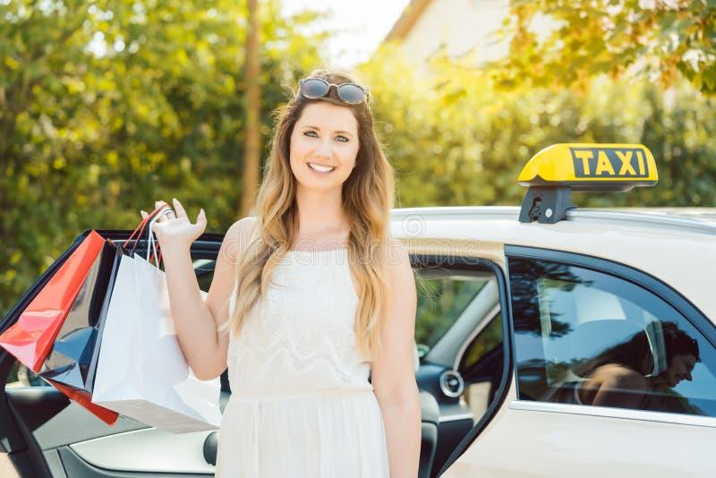 El salir de la mujer de los bolsos de compras del coche del taxi que llevan fotografía de archivo