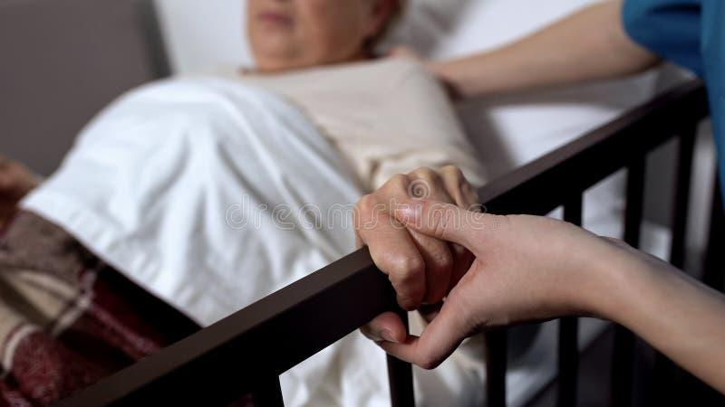 El salir maduro de la mujer de la cama con la ayuda de la enfermera en la primera vez despu?s de cirug?a fotos de archivo