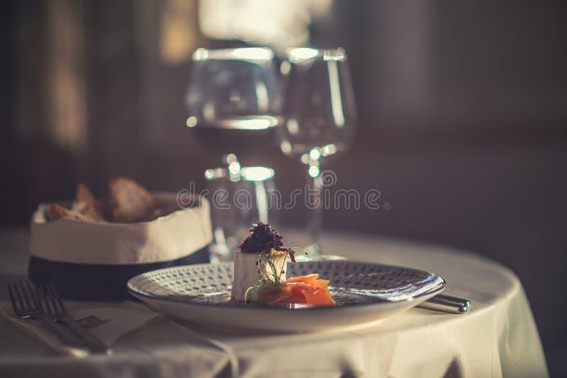 El salmón ahumado con queso, la cebolla y las hierbas sirvió en la placa con la copa de vino y la tostada, gastronomía moderna imagen de archivo libre de regalías