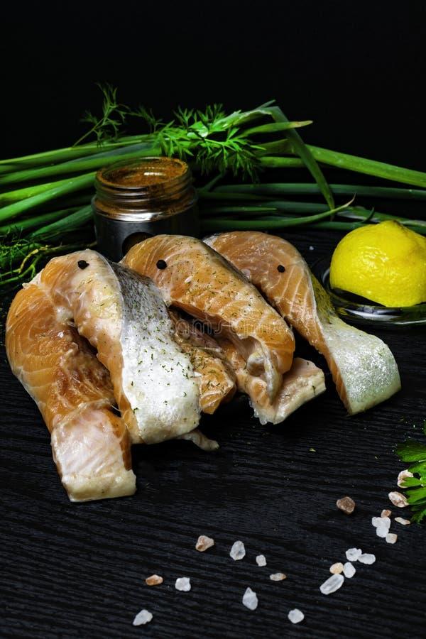 el salmón crudo en el filete con las especias, cebolla verde, pimienta, limón, perejil, eneldo, sal, selery de la trucha se pone  imagenes de archivo