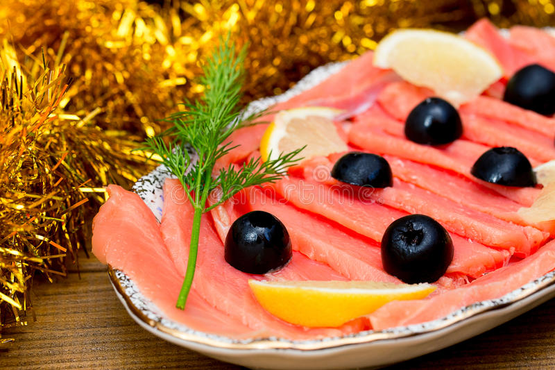 El salmón rojo cortado de los pescados pone verde aceitunas negras del limón en la placa, fondo marrón de madera, visión superior fotografía de archivo