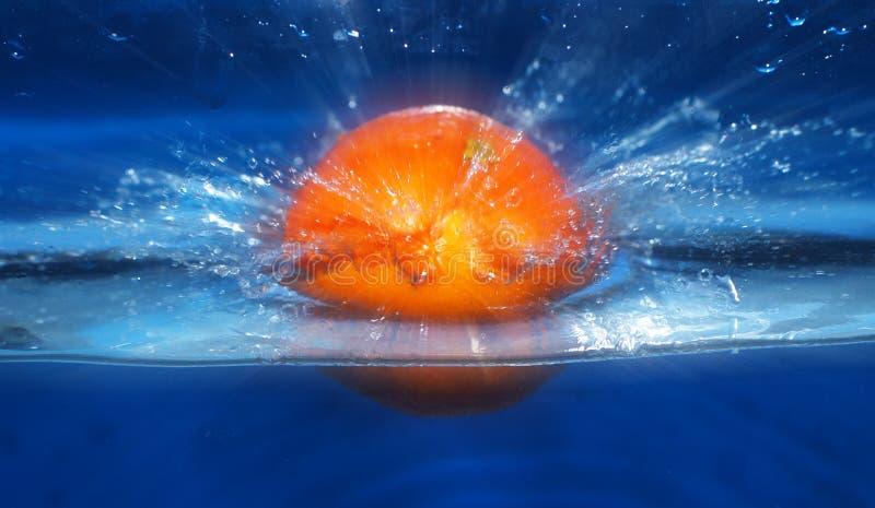 El salpicar anaranjado en fondo del azul del agua fotos de archivo