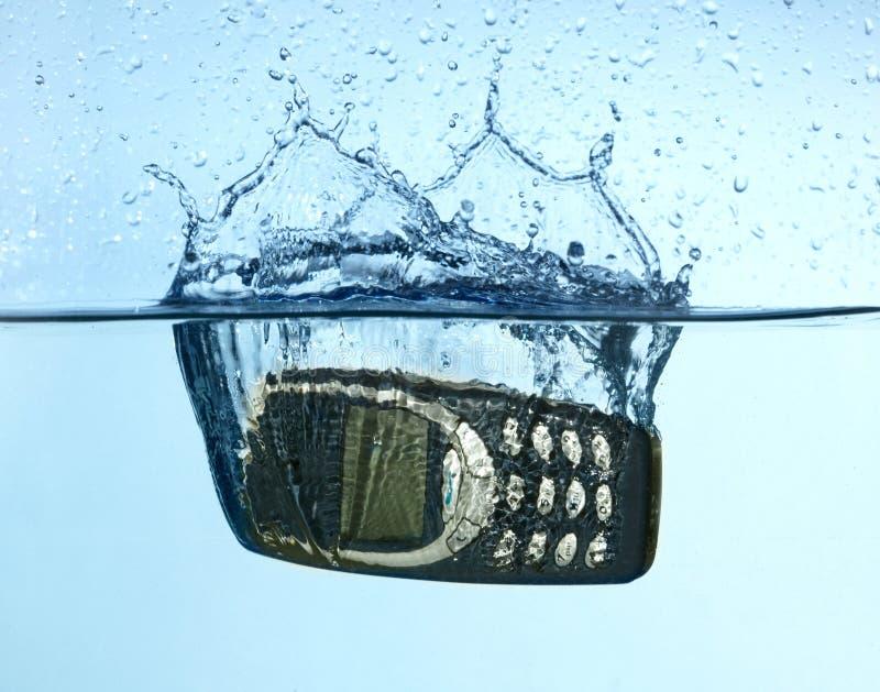 El salpicar celular en el agua foto de archivo