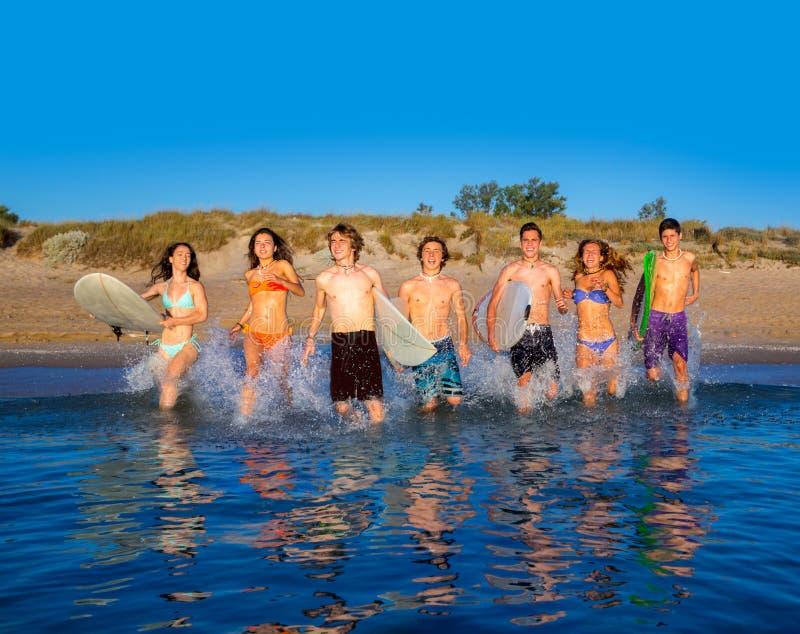 El salpicar corriente de la playa del grupo de las personas que practica surf del adolescente imagenes de archivo