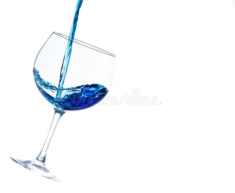 El salpicar líquido en un vidrio de cóctel en un fondo blanco fotos de archivo
