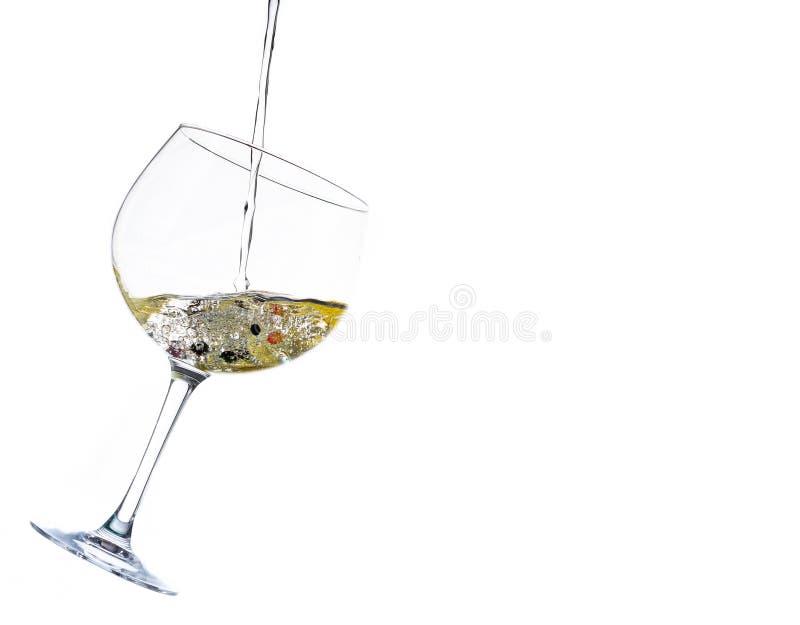 El salpicar líquido en un vidrio de cóctel en un fondo blanco imágenes de archivo libres de regalías