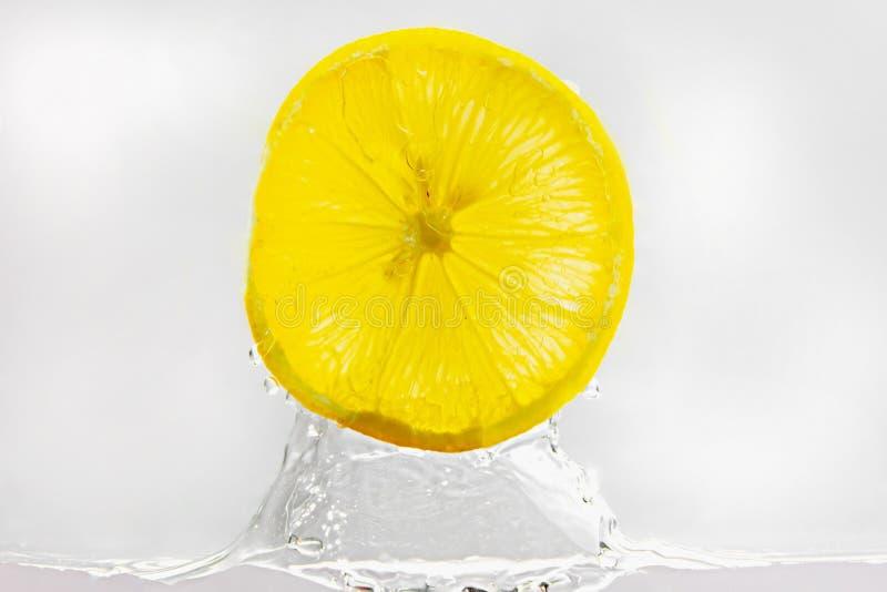 El saltar de la rebanada del limón del agua en el fondo blanco foto de archivo
