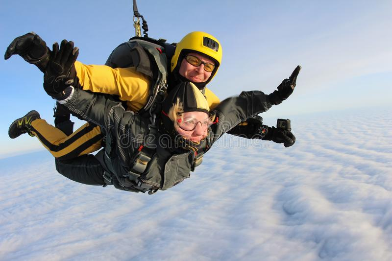 El saltar en caída libre en tándem Los Skydivers están volando sobre las nubes blancas foto de archivo