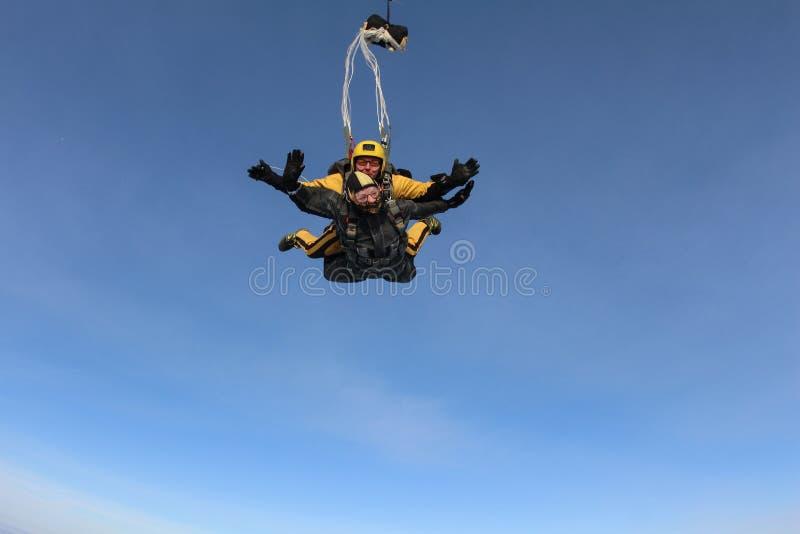 El saltar en caída libre en tándem Los Skydivers están volando sobre las nubes blancas imagen de archivo