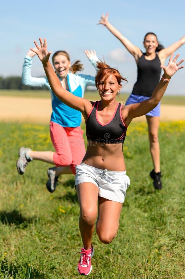 El salto alegre de los amigos disfruta de funcionamiento del deporte del verano imagen de archivo