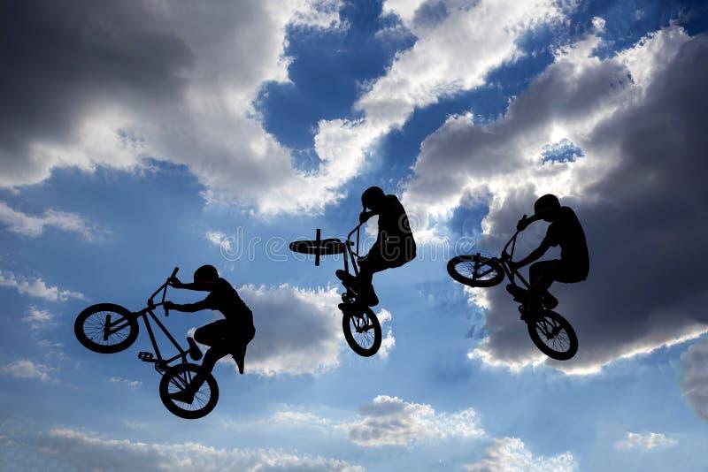 El salto de la bici siluetea la exposición múltiple foto de archivo