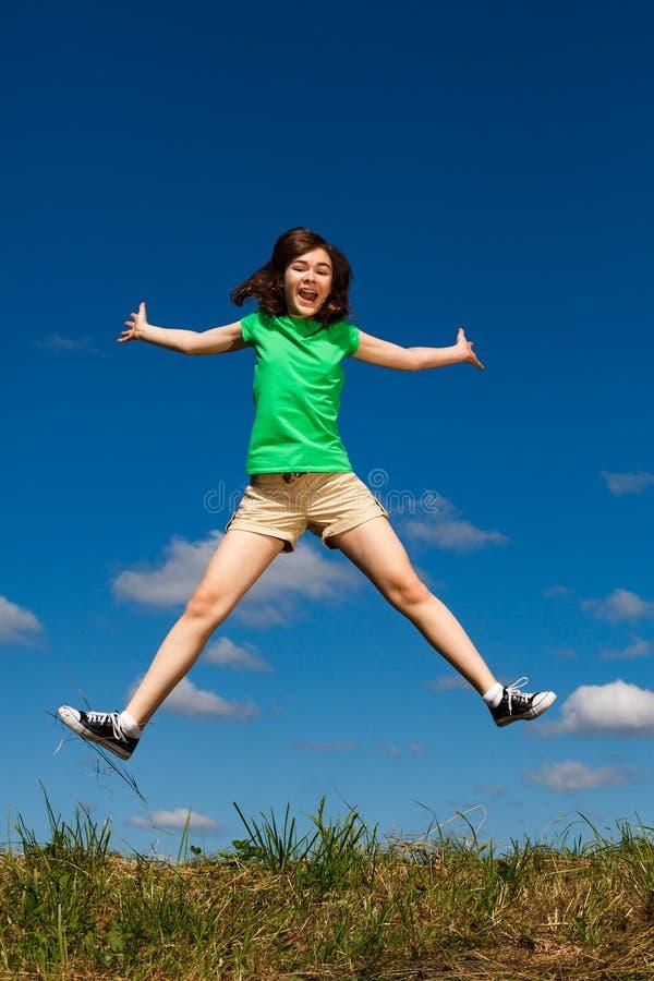 El salto de la muchacha, corriendo contra el cielo azul imágenes de archivo libres de regalías