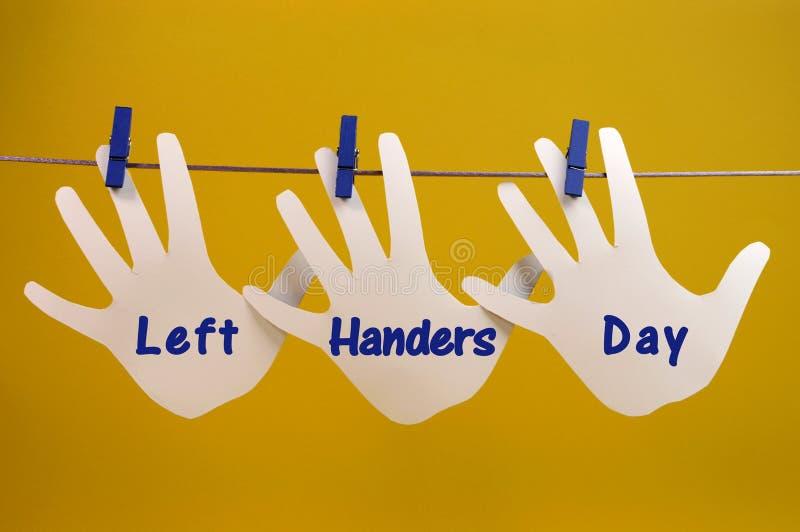 El saludo del mensaje del día de los zurdos a través de la silueta de la mano izquierda carda la ejecución de clavijas en una líne fotos de archivo libres de regalías