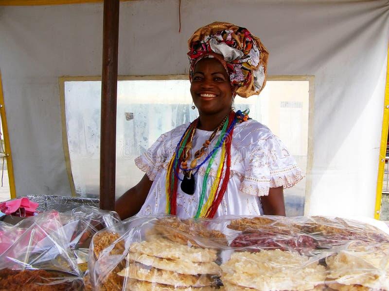 El Salvador, Brasil November-11 th 2016 A mulher brasileira da ascendência africana que veste a roupa tradicional vende cookies imagem de stock