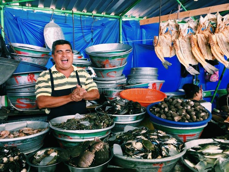 EL SALVADOR LA LIBERTAD - MARS 4, 2017 Fiskmarknaden, en man som säljer skaldjur, skrattar och erbjuder genuint hans gods, kommun arkivfoton