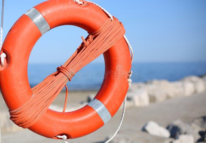 El salvavidas anaranjado para la gente acerca a rocas en el mar imagenes de archivo