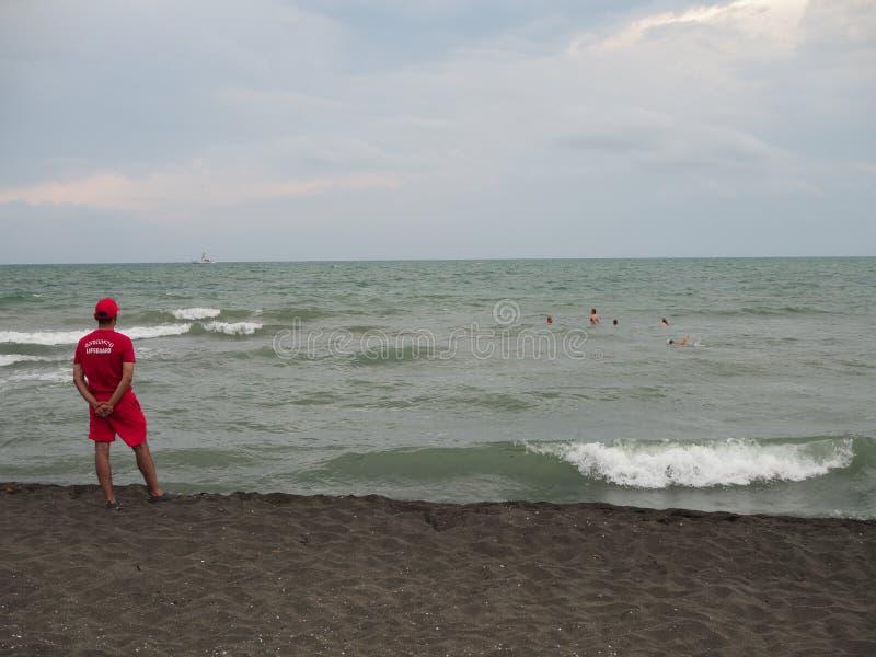 El salvavidas en la orilla del mar que mira a los bañistas en la tormenta de los turistas Georgia, Ureki - junio de 2019 fotos de archivo