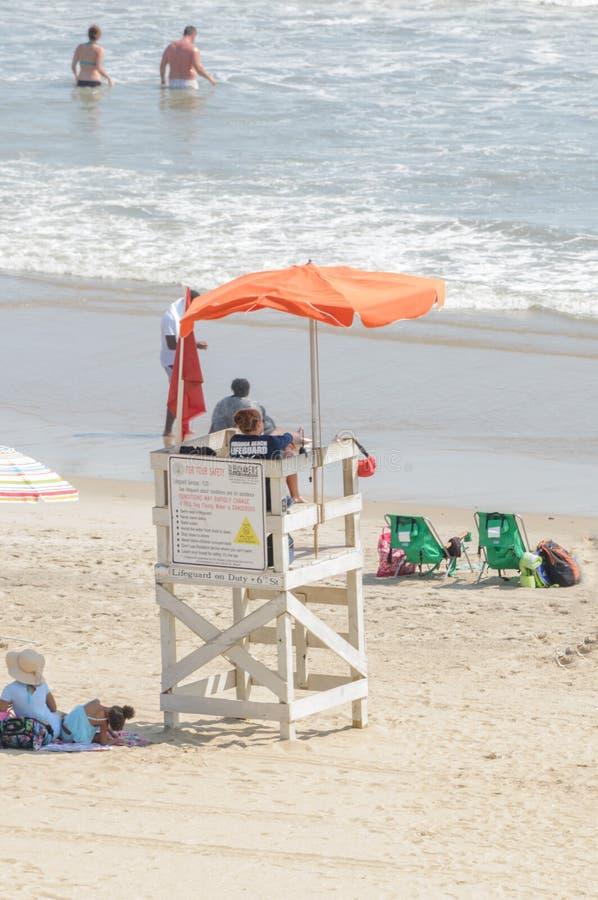 El salvavidas mira a los bañistas de una cabina del salvavidas en Virginia Beach, VA fotografía de archivo
