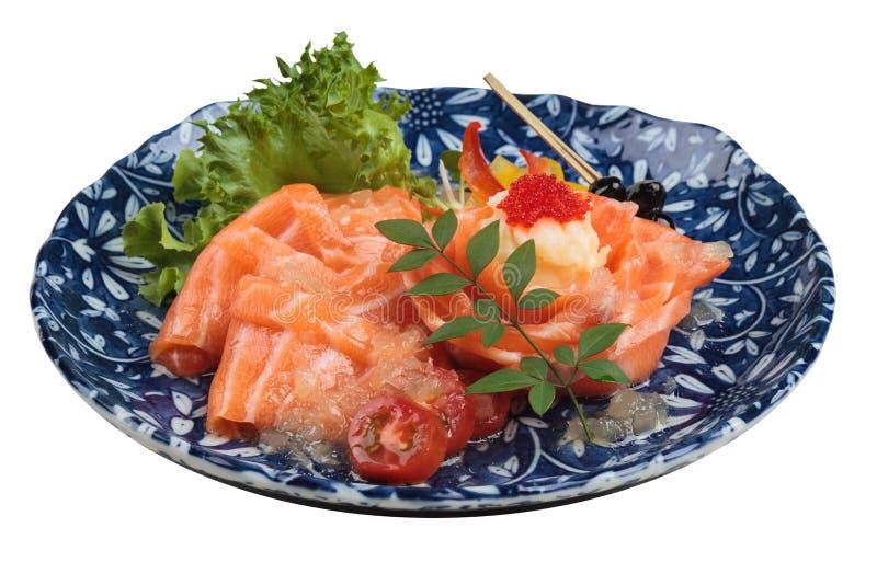 El sashimi de color salmón aislado sirvió con la salsa de la cal, la ensalada de patata y el ikura servidos en placa jadeada de l foto de archivo libre de regalías