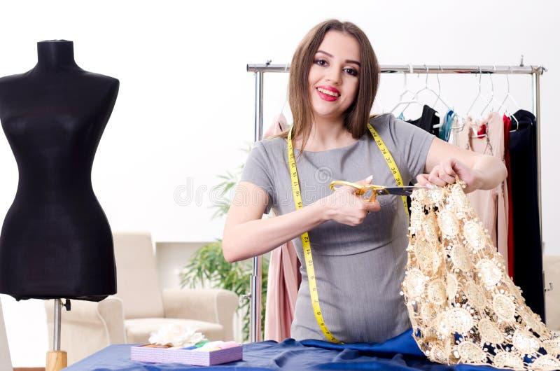 El sastre de sexo femenino hermoso joven que toma medidas foto de archivo libre de regalías