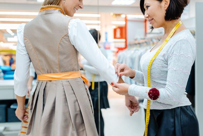 El sastre que cabía a anunció el vestido a un cliente de la mujer fotos de archivo libres de regalías