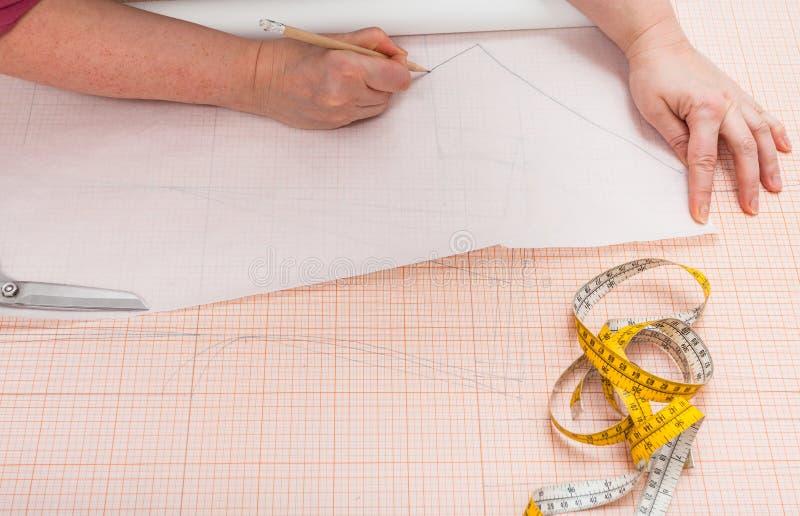 El sastre remonta un modelo de la ropa en el papel de trazo imagen de archivo