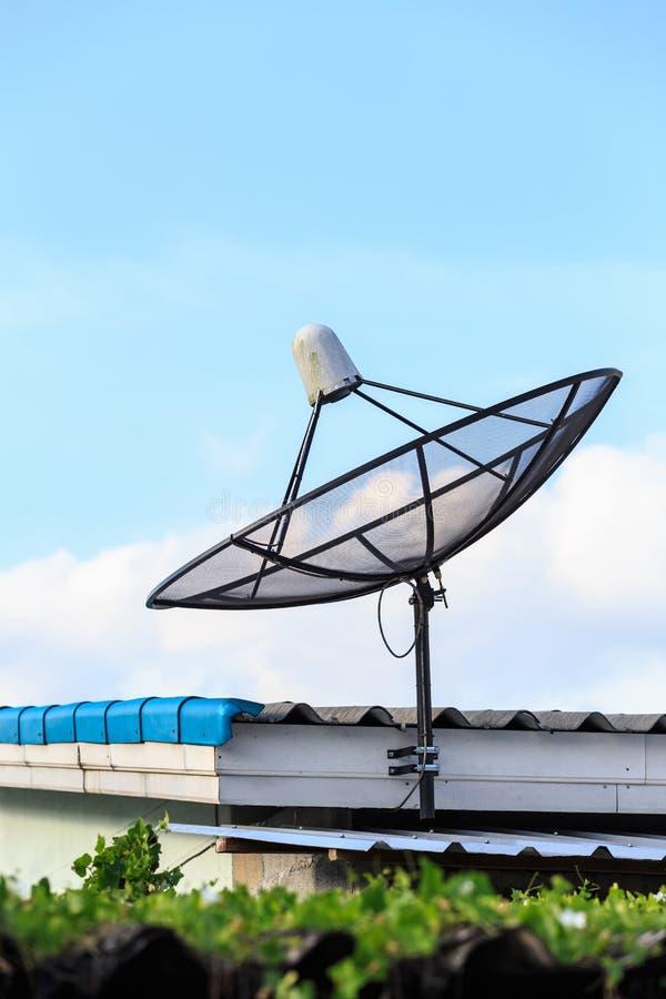 El satélite negro instala en el tejado de la casa con el cielo azul imágenes de archivo libres de regalías