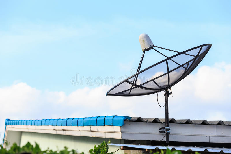 El satélite negro instala en el tejado de la casa con el cielo azul fotos de archivo