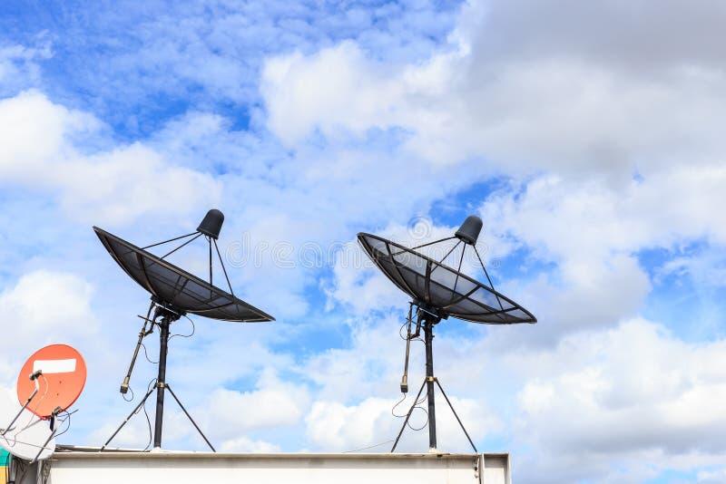 El satélite negro instala en el tejado de la casa con el cielo azul fotos de archivo libres de regalías