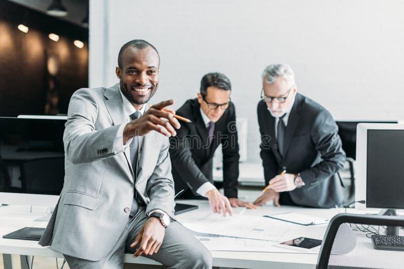 el señalar afroamericano sonriente del hombre de negocios ausente mientras que colegas del negocio que discuten el trabajo fotos de archivo