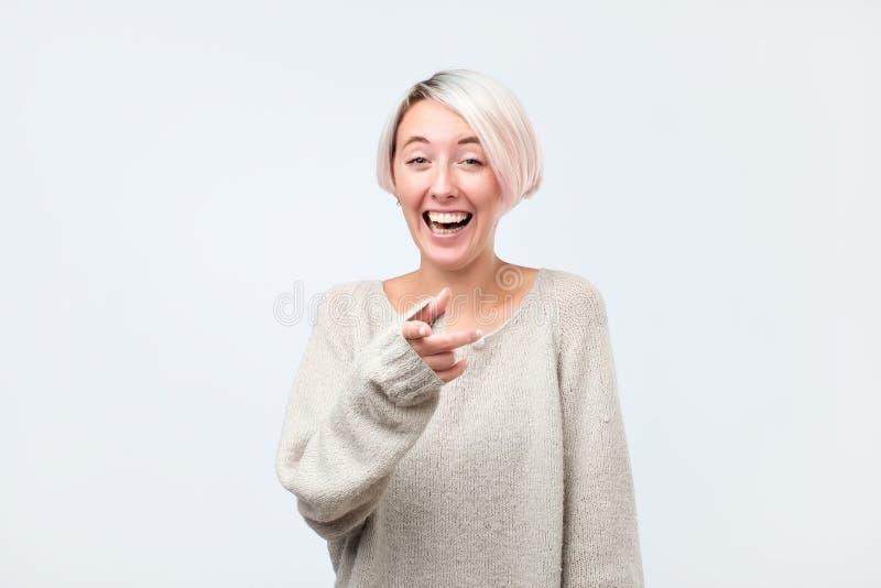 El señalar de risa de la mujer joven en la cámara Es una gran broma imágenes de archivo libres de regalías