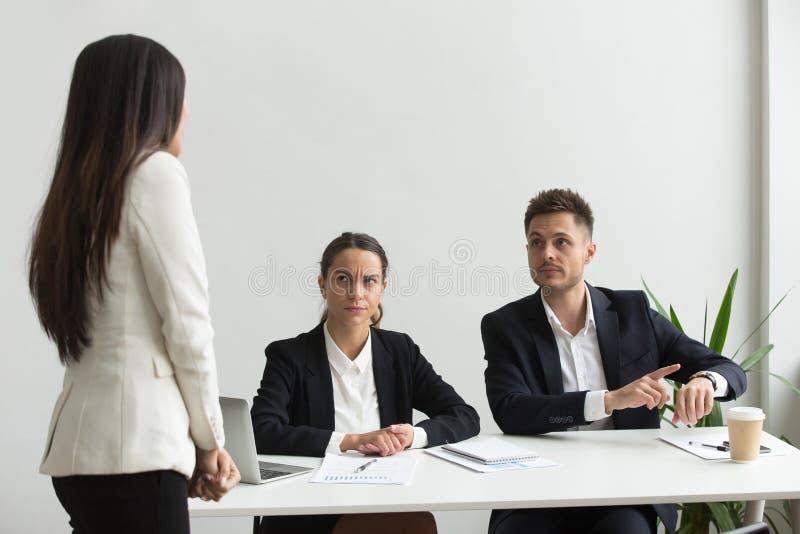 El señalar ejecutivo enojado en el reloj que regaña al empleado para el bei foto de archivo