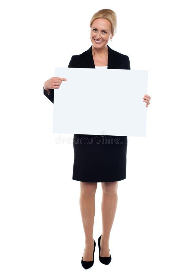 El señalar ejecutivo femenino hacia la tarjeta blanca del anuncio imagen de archivo