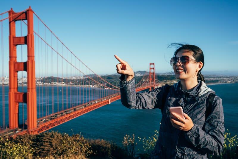 El señalar emocionado turista de la muchacha en el cielo azul fotografía de archivo libre de regalías