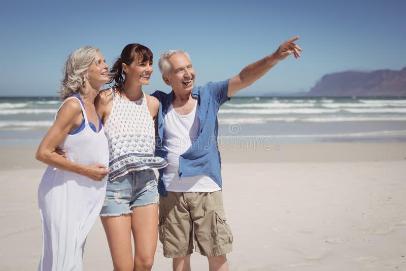 El señalar feliz del hombre mayor ausente mientras que se coloca con la familia en la playa foto de archivo libre de regalías
