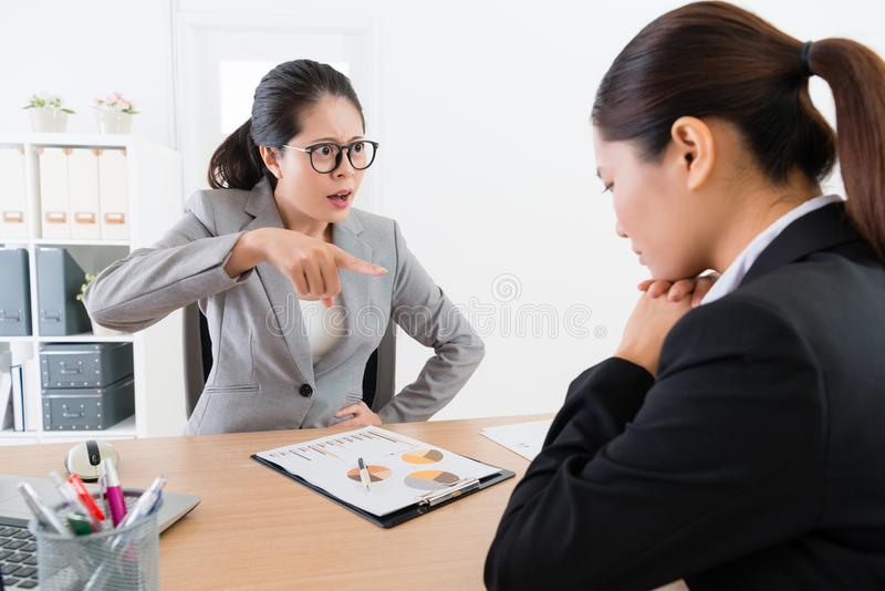 El señalar femenino enojado del encargado culpa a su empleado foto de archivo libre de regalías